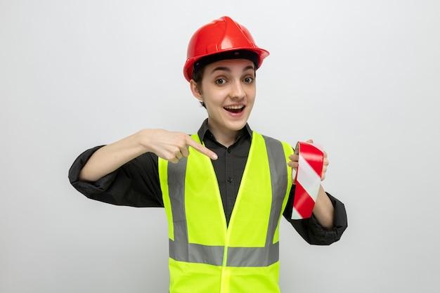 Junge baumeisterin in bauweste und schutzhelm, die klebeband hält und mit dem zeigefinger darauf zeigt, glücklich und fröhlich lächelnd