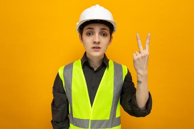 Junge baumeisterin in bauweste und schutzhelm, die mit ernstem gesicht aussieht und nummer zwei mit den fingern zeigt