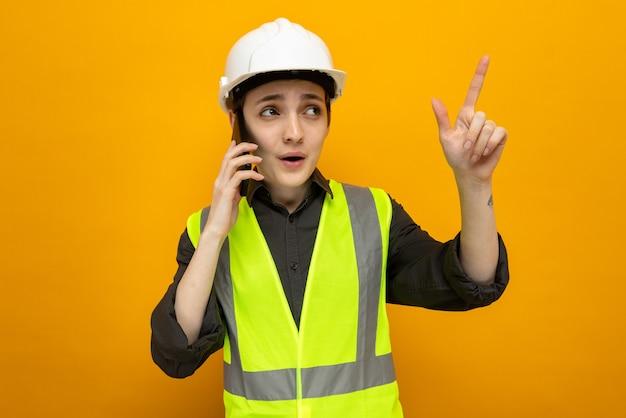 Junge baumeisterin in bauweste und schutzhelm, die verwirrt aussieht und mit dem zeigefinger auf etwas zeigt, während sie mit dem handy über der orangefarbenen wand spricht