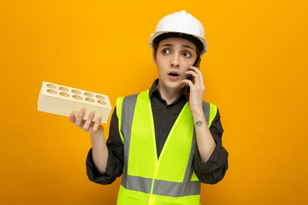 Junge baumeisterin in bauweste und schutzhelm, die ziegelsteine hält, die verwirrt aussehen, während sie auf dem handy über der orangefarbenen wand telefoniert?