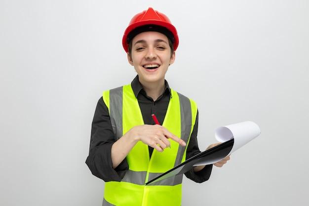 Junge baumeisterin in bauweste und schutzhelm, die zwischenablage mit leeren seiten hält und mit dem zeigefinger auf die zwischenablage zeigt, die fröhlich lächelt