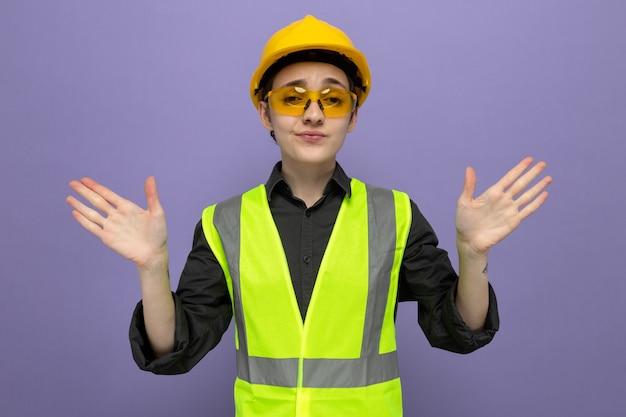 Junge baumeisterin in bauweste und schutzhelm mit gelber sicherheitsbrille verwirrt und unzufrieden, die hände über der blauen wand stehend zu heben