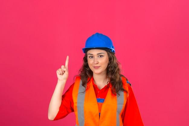Junge baumeisterin in der bauuniform und im sicherheitshelm, der mit neuem ideenkonzept des fingers über isolierte rosa wand zeigt