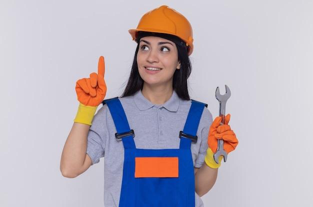 Junge baumeisterin in der bauuniform und im sicherheitshelm, die gummihandschuhe halten schlüssel halten, der zeigefinger zeigt, der lächelnd über weißer wand steht
