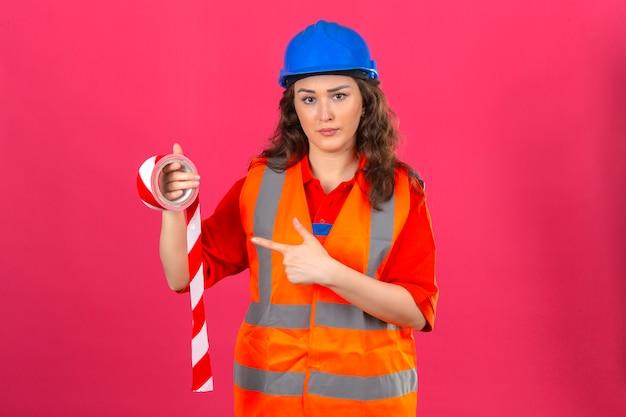 Junge baumeisterin in der bauuniform und im sicherheitshelm, die mit klebeband stehen und mit zeigefinger zeigen, der über isolierter rosa wand die stirn runzelt
