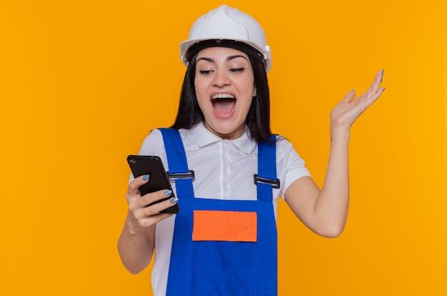 Junge baumeisterin in der bauuniform und im sicherheitshelm, die smartphone halten, das es glücklich und aufgeregt mit dem arm angehoben betrachtet, der über orange wand steht