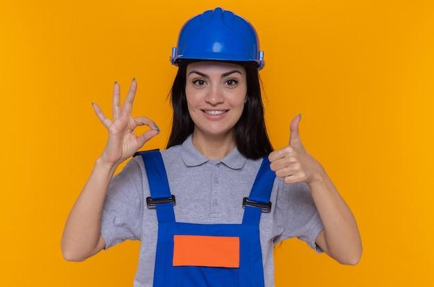Junge baumeisterin in der bauuniform und im sicherheitshelm, die vorne glücklich und positiv betrachten, zeigen daumen oben und ok zeichen, das über orange wand steht