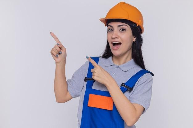 Junge baumeisterin in der bauuniform und im sicherheitshelm, die vorne glücklich und positiv lächelnd zeigen, mit zeigefingern auf die seite stehend über weißer wand