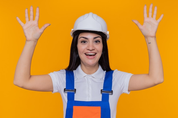 Junge baumeisterin in der bauuniform und im sicherheitshelm, die vorne lächelnd fröhlich glücklich und positiv mit den armen betrachten, die über orange wand stehen