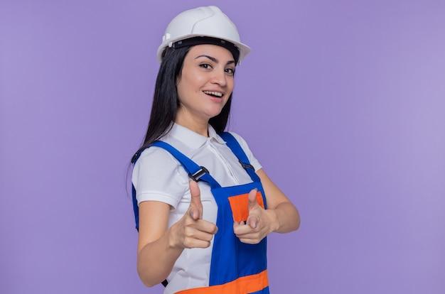 Junge baumeisterin in der bauuniform und im sicherheitshelm lächelnd, die fröhlich mit zeigefingern an der front stehend über lila wand zeigen