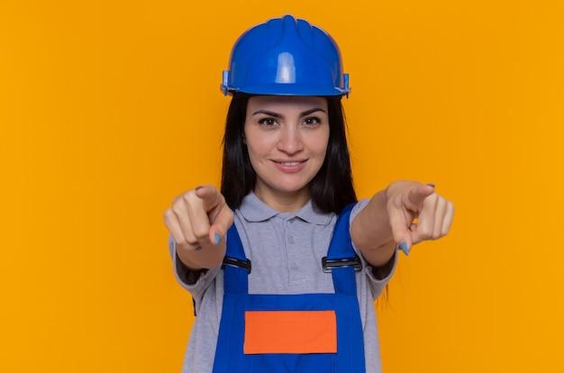 Junge baumeisterin in der bauuniform und im sicherheitshelm lächelnd, die sicher zeigen, dass mit beiden händen zeigefinger vorne über orange wand stehen