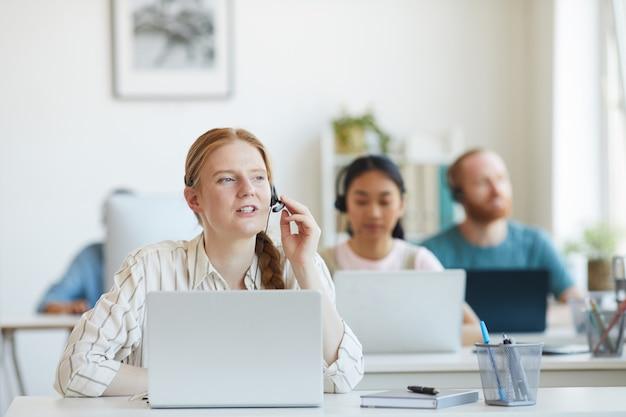 Junge bedienerin in kopfhörern im gespräch mit dem kunden im kundenservice mit ihren kollegen