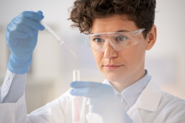 Junge behandschuhte wissenschaftlerin oder laborarbeiterin in brillen, die flüssigkeit von der pipette in den kolben mit rosa flüssiger substanz fallen lassen