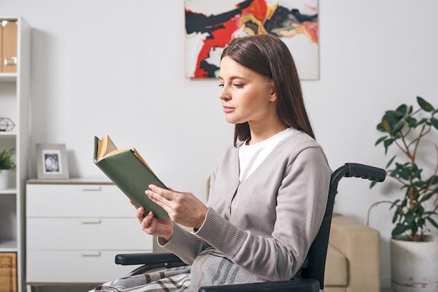 Junge behindern brünette frau in der freizeitkleidung, die im rollstuhl sitzt und buch liest, während tag zu hause verbringen