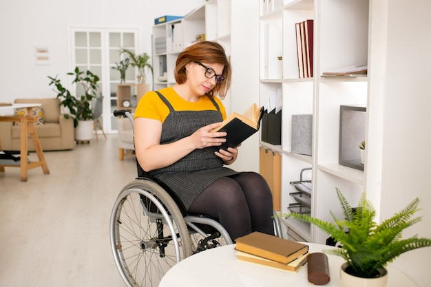 Junge behindern frau in der freizeitkleidung und in den brillen, die auf rollstuhl durch regal sitzen und buch lesen, während heimunterricht erhalten