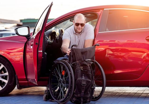 Junge behinderte fahrer, die in rotes auto vom rollstuhl einsteigen