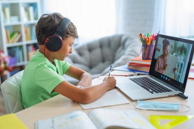 Junge benutzt einen laptop, um mit seinem lehrer einen videoanruf zu tätigen