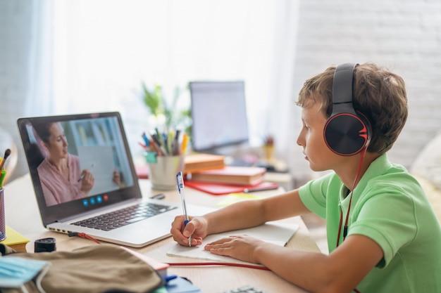 Junge benutzt laptop, um videoanruf mit seinem lehrer zu machen