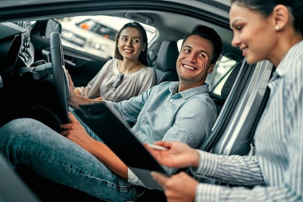 Junge beraterin und paarkäufer sitzen im neuwagen und unterzeichnen einen vertrag in der autoshow. konzept für die autovermietung.