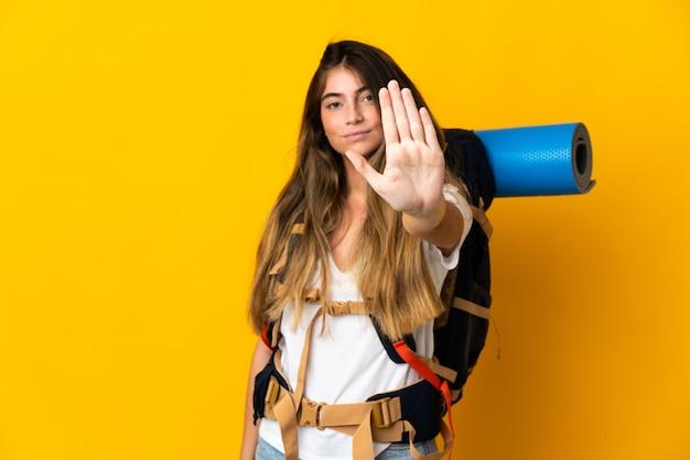 Junge bergsteigerfrau mit einem großen rucksack auf gelb, der stoppgeste macht