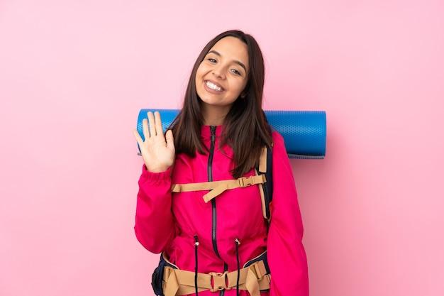 Junge bergsteigerfrau mit einem großen rucksack auf lokalisiertem rosa gruß mit hand mit glücklichem ausdruck