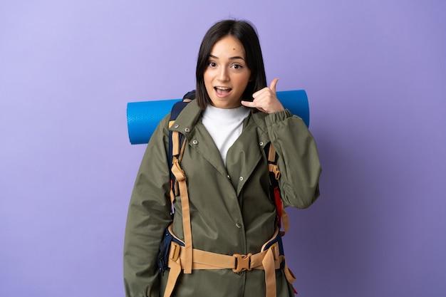 Junge bergsteigerfrau mit einem großen rucksack über isolierter wand, die telefongeste macht. rufen sie mich zurück zeichen
