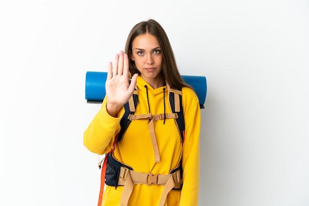 Junge bergsteigerfrau mit einem großen rucksack über lokalisiertem weißem hintergrund, der stoppgeste macht