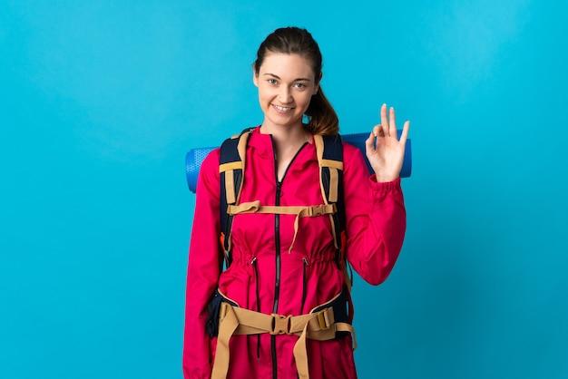 Junge bergsteigerfrau über isoliertem blauem hintergrund, die ein ok-zeichen mit den fingern zeigt