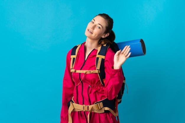 Junge bergsteigerfrau über isolierter blauer wand, die mit hand mit glücklichem ausdruck salutiert