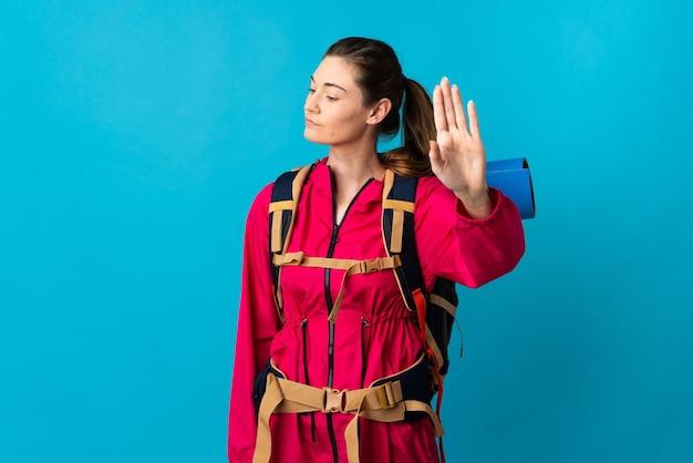Junge bergsteigerfrau über isolierter blauer wand, die stoppgeste macht und enttäuscht