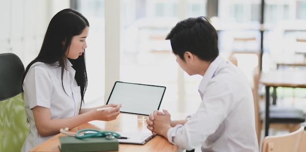 Junge berufsärztin, die zustand und symptome ihrem patienten erklärt