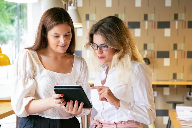 Junge berufsfrauen, die zusammen stehen und design auf dem bildschirm beobachten