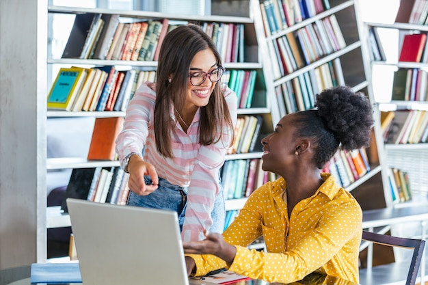 Junge berufstätige arbeiten in unternehmen mit laptop und tablet