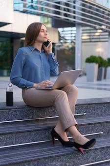 Junge berufstätige frau, die auf treppe vor glasgebäude sitzt, laptop im schoß hält und auf handy spricht