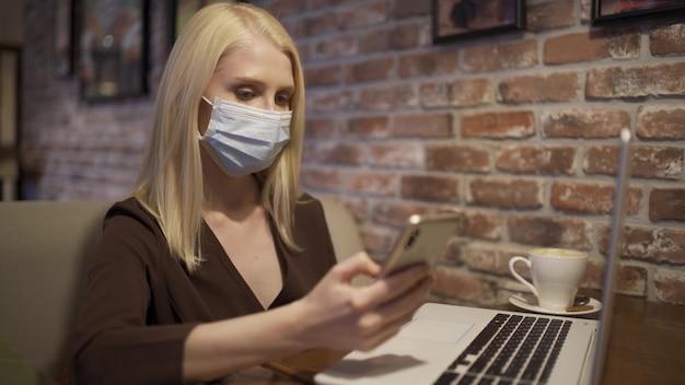 Junge berufstätige frau in einer medizinischen maske scrollt das telefon in einem gemütlichen café. auf dem tisch steht ein laptop. eine frau arbeitet in einem café. nahaufnahme, 4k uhd.