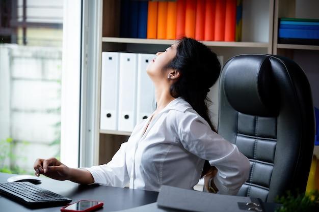 Reifer mann der im stuhl leiden unter rückenschmerzen bei der anwendung auf laptop sitzt