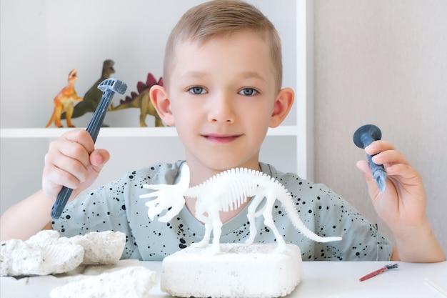 Junge beschäftigt sich mit der ausgrabung von dinosauriern. lernspiel mit kindern. ein kind gräbt die knochen eines dinosauriers aus. entwicklung von ausdauer und feinmotorik. glücklicher junge