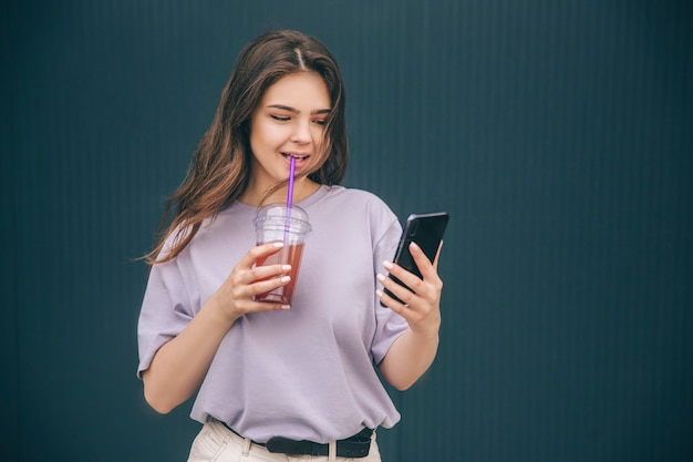Junge beschäftigte frau, die smartphone in der hand betrachtet und rote limonade trinkt
