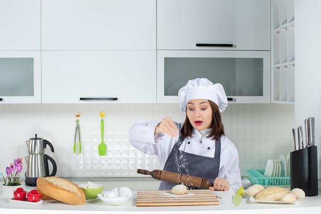 Junge beschäftigte köchin in uniform, die hinter dem tisch steht und gebäck in der weißen küche zubereitet