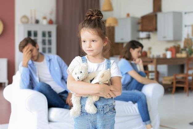 Junge beschimpfte eltern sitzen sich auf der couch gegenüber, während die kleine wehrlose tochter verärgert in die kamera schaut.