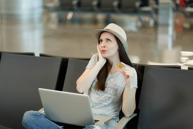 Junge besorgte reisende touristenfrau, die am laptop arbeitet, bitcoin hält, denkt und die hand in der nähe des gesichts hält, wartet in der lobbyhalle am flughafen?