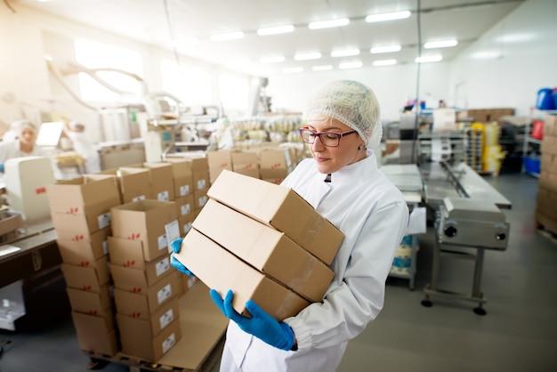 Junge besorgte vorsichtige schöne weibliche arbeiterin, die einen schweren stapel kisten im fabriklagerraum trägt.
