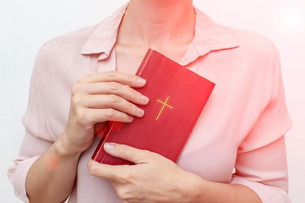 Junge betende christliche frau, die heilige bibel mit einem kreuz hält