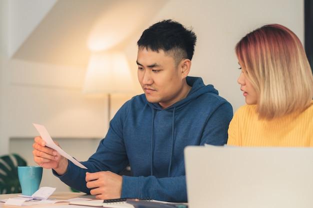 Junge betonten die asiatischen paare, die finanzen verwalten und ihre bankkonten unter verwendung der laptop-computers wiederholen