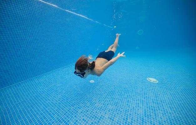 Junge bewegt sich im blauen schwimmbad