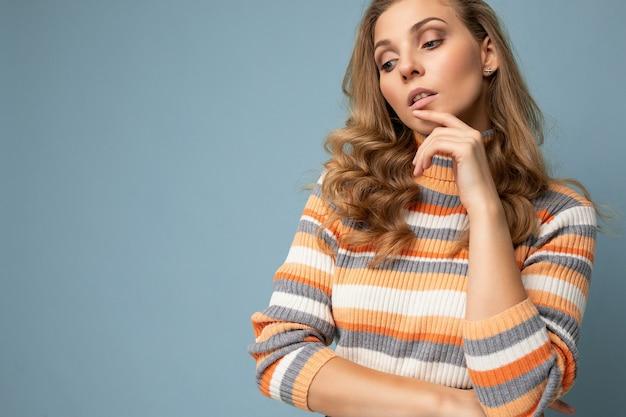 Junge bezaubernde faszinierende schöne sexy positive blonde frau, die beiläufigen gestreiften pullover einzeln auf blauem hintergrund mit freiem raum trägt.
