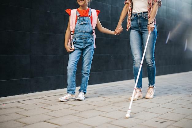 Junge blinde mutter, die mit ihrer kleinen tochter auf der stadtstraße spaziert. sie tragen gesichtsschutzmasken. zurück zur schule und neues coronavirus-lifestyle-konzept.