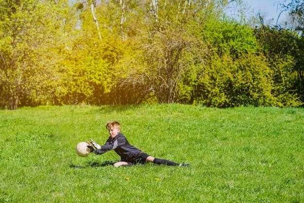 Junge blockiert den ball mit den händen