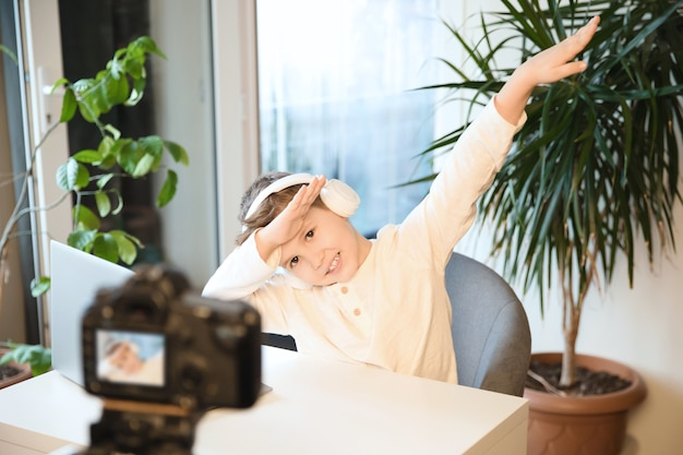 Junge blogger, der video für seinen kanal aufzeichnet. netter kinderjunge, der cooles zeichen zeigt und zur videokamera schaut.