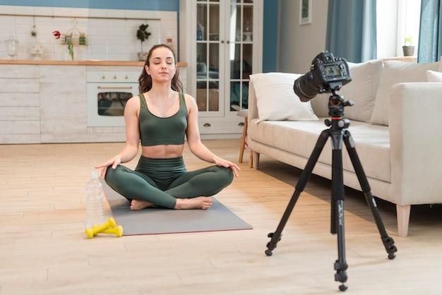 Junge blogger, die yoga-sitzung aufzeichnet